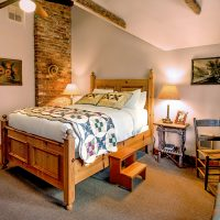 Lodge room #4 has a queen bed and vaulted ceilings with lodgepole trusses